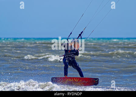 Kite boarder starting to fly over the sea during a windy day in french riviera - Stock Image