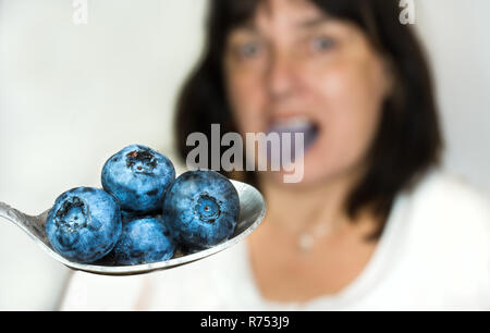 Blue juicy bilberries on spoon close-up. Blurry woman in background. Stainless spoonful of fresh ripe blueberry fruits. Female face with purple tongue. - Stock Image