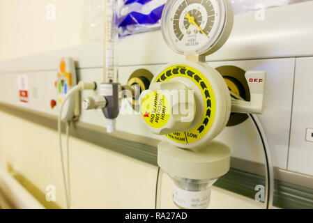 Bed head unit in a hospital ward showing a suction vacuum pressure gauge, an oxygen supply and a nurses call bell. - Stock Image