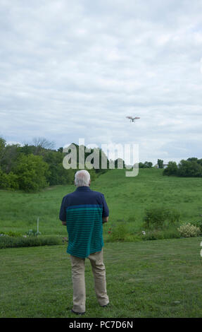 Man operating a dji Phantom Quadcopter Drone unmanned aerial vehicle in flight over open field. - Stock Image