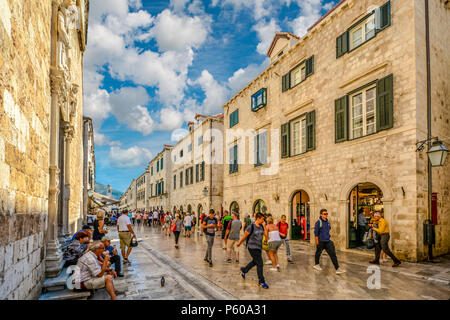 Tourists walk the stradun, main street in the historic walled city of Dubrovnik on a sunny, warm day on the Adriatic coast of Croatia - Stock Image