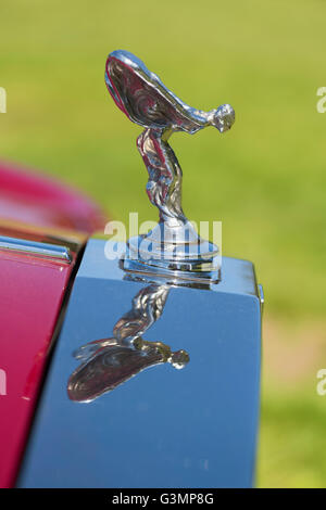 Westbury, New York, USA. June 12, 2016.  Flying Lady chrome hood ornament is reflected atop grille of 1985 red Rolls - Stock Image