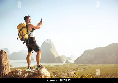 Backpacker tourist stands on big rock and takes mobile photo at viewpoint - Stock Image