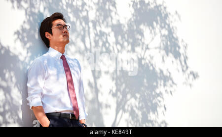 Businessman relaxing leaning against a wall - Stock Image