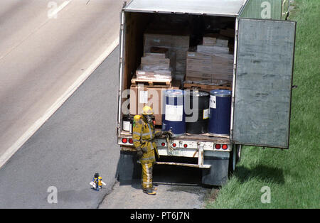 Firefighters examine hazardous cargo in the back of a tractor trailer on I95 in Beltsville, Md - Stock Image