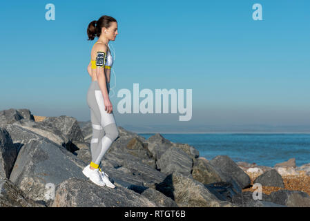 woman wearing sportswear standing on rocks by the sea listening to music on her phone on her armband. - Stock Image
