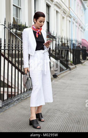 Woman in linen suit looking at phone in street, full length - Stock Image