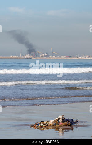Pollution on the beach at Agadir Morocco Africa. Washed up fishing nets and clothing in the foreground with pollution into the sky from the harbour - Stock Image