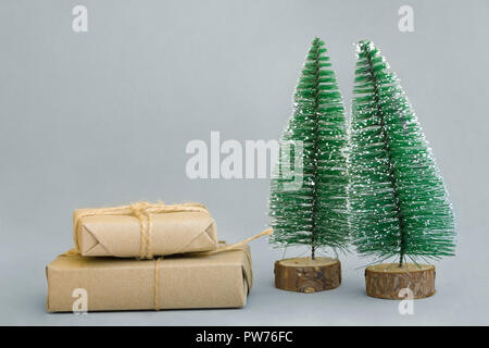 Stacked gift boxes wrapped in craft paper tied with twine Christmas trees on grey background. New Year corporate presents shopping concept. Poster ban - Stock Image