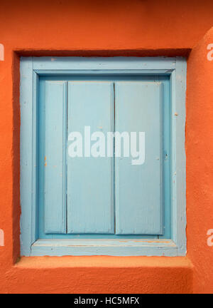 a blue wooden door or shutter in an orange wall - Stock Image