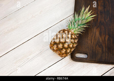 Fresh ripe pineapple on a white wooden background, top view. From above. Right - Stock Image