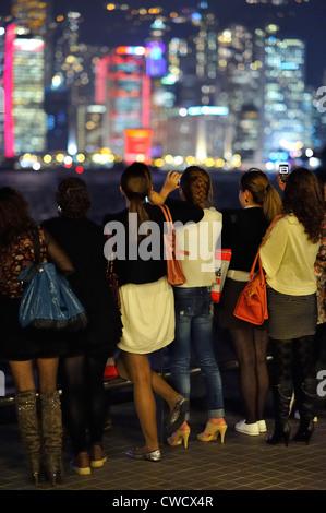 Young women looking at the night skyline, Hong Kong SAR - Stock Image