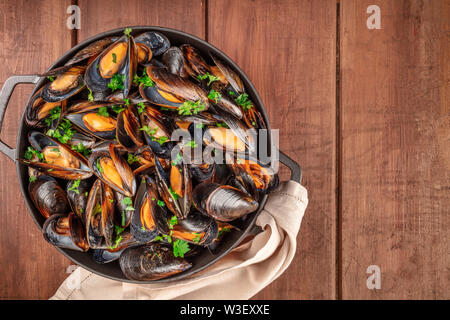 Marinara mussels, moules mariniere, in a cooking pot, overhead view, shot from the top on a dark rustic wooden background with a place for text - Stock Image