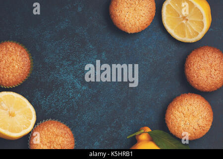 Lemon muffins, fresh lemons on a blue background. View from above. copy space. Toning - Stock Image