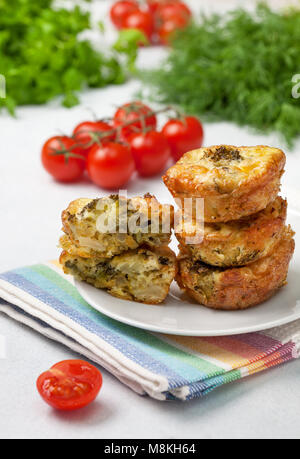healthy breakfast. broccoli cheese bites (muffins), fresh tomatoes, fresh herbs on light concrete background - Stock Image