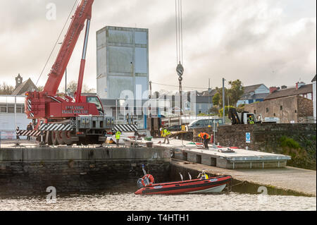 Schull, West Cork, Ireland. 16th Apr, 2019. West Cork Civil Engineering were given the task of refloating the €600,000 Schull pontoon, ready for the season.  Workers are seen preparing to lift a piece of the pontoon into the water. Credit: Andy Gibson/Alamy Live News. - Stock Image