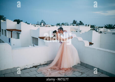 Happy newlyweds kiss on the roof of white house against background of blue sky during the honeymoon in Egypt. - Stock Image