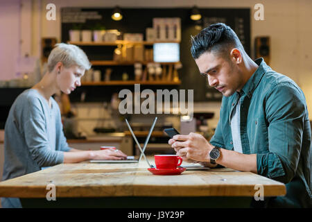 man and woman working on laptops at table in cafe - Stock Image
