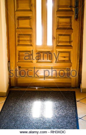 Wooden entrance door with sunlight shining on a - Stock Image