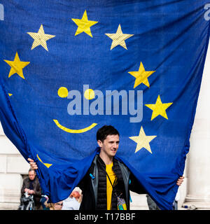 London, UK. 23 March 2019. Young man holding up an EU flag with a smiley face. Remain supporters and protesters take part in a march to stop Brexit in Central London calling for a People's Vote. - Stock Image