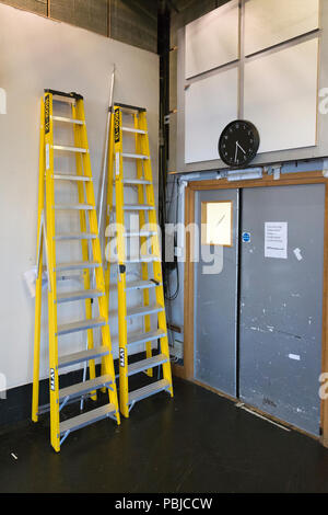 Two yellow step ladders resting against a wall. - Stock Image