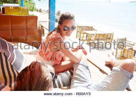 Young woman wearing sunglasses on porch - Stock Image