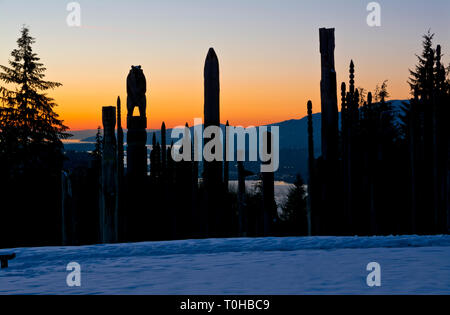 Burnaby Mountain Park in Winter.  'Playground of the Gods' Japanese Ainu totem carvings sculptures, at sunset in Burnaby, BC, Canada. - Stock Image