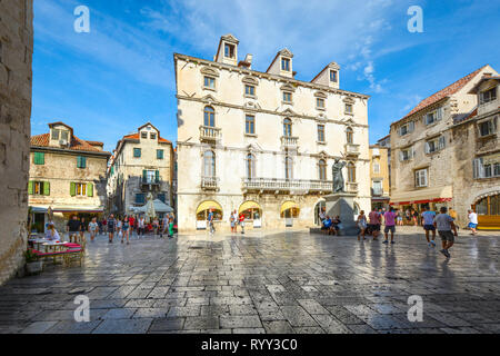 Visitors pass through Trg Brace Radic or the Fruit Square with shops and outdoor cafes on a sunny summer day in Split Croatia - Stock Image