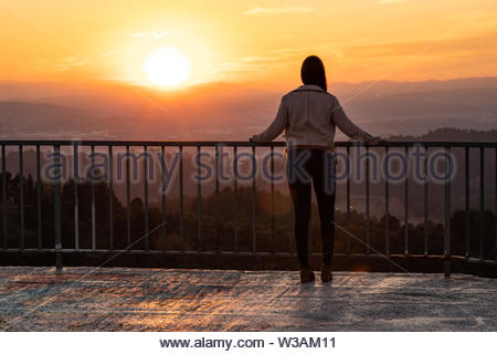 Beautiful woman back shot on a viewpoint railing during sunset with blurred background and copy space - Stock Image