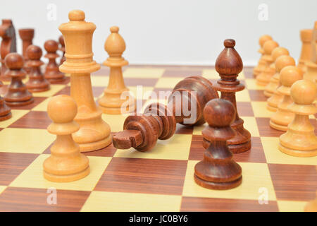 King at the foot of various pieces on the chessboard - Stock Image