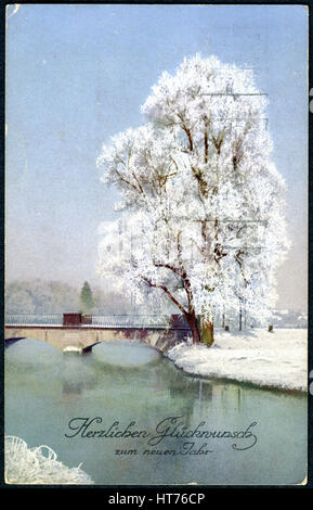 A Christamas postcard printed in Switzerland shows a winter landscape. The inscription in German: Happiness in the - Stock Image