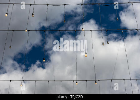 Illuminated electric bulbs hang from black wires against the background of deep blue sky and white and grey clouds - Stock Image