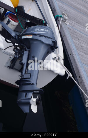 Yamaha outboard motor, up out of the water, attached to small boat secured at Lochinver harbour, Scotland - Stock Image