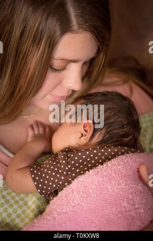 Mother holding a new born baby. - Stock Image