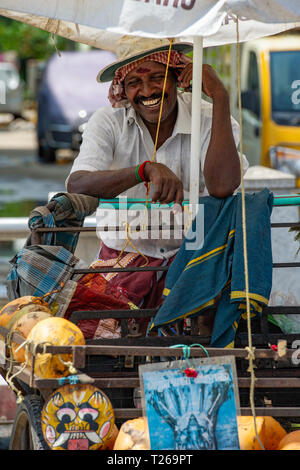 A smiling man in the street market selling coconut milk straight out of the shell - Stock Image