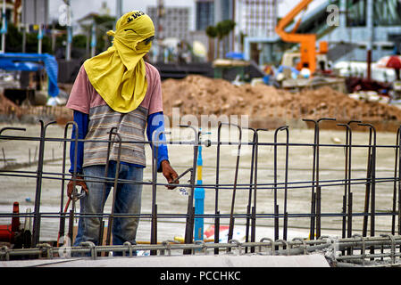 Thailand construction worker wearing heat protection head cover and facemask - Stock Image