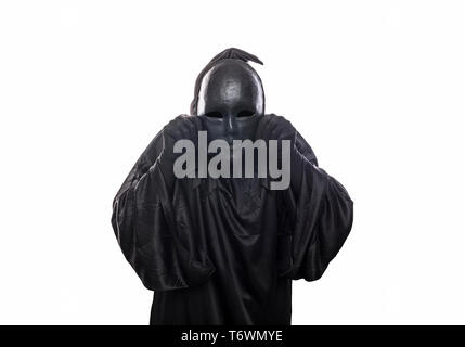 Scary figure in hooded cloak with mask in hand isolated on white background - Stock Image