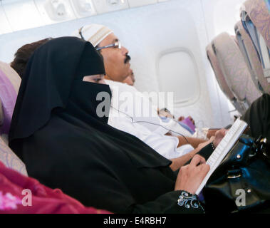 A muslim woman on a plane wearing a niqab - Stock Image