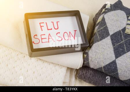 Flu season - text in frame. Background - warm woolen clothes - Stock Image