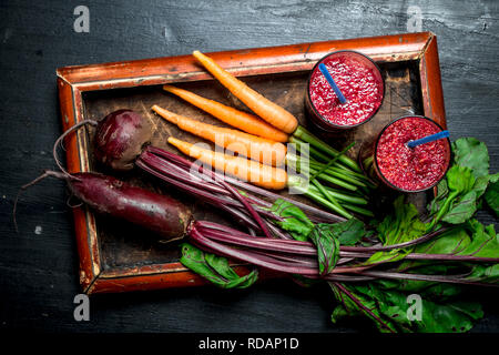 Vegetable smoothie with beets and carrots. On black background. - Stock Image