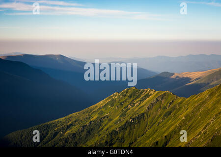 Mountainside with green grass, other mountain ranges in shadow and fog, peaks with blue sky in a background, Carpathian - Stock Image