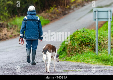 Bantry, West Cork, Ireland. 14th Apr, 2019. A woman walks her dog in the rain in Bantry this afternoon.  County Cork is currently in the midst of a Status Yellow Rainfall and Wind Warning which lasts until 6pm Monday. Credit: Andy Gibson/Alamy Live News. - Stock Image