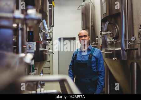 Confident owner standing amidst manufacturing equipment - Stock Image
