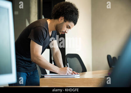 Young man writing - Stock Image