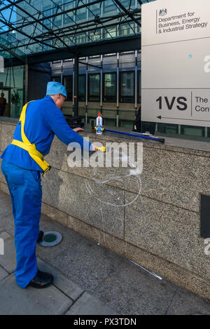 London, UK. October 19th, 2018. 'Commander Neil Godwin Tracy' of International Rescue smoothes the paste on the wall of  the Dept for Business, Energy and Industrial Strategy (BEIS) after he had been refused entry. He had come to offer his organisation's assistance, to produce policies which which recognise the desperate need to cut carbon emissions to avoid disastrous global warming and climate change by banning all fracking. Credit: Peter Marshall/Alamy Live News - Stock Image