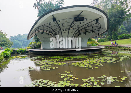 Singapore botanic gardens, outdoor stage located in the garden surrounded by a pond - Stock Image