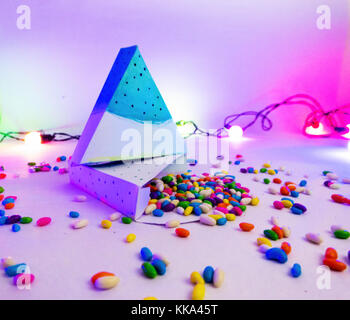 Christmas decoration triangle git box with candies for celebration with multi color lights best Christmas holidays - Stock Image