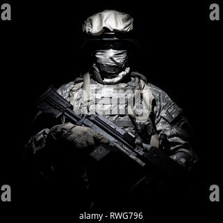 U.S. Armed forces soldier wearing a mask, armed with a machine gun. - Stock Image
