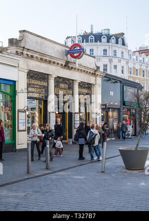 People coming and going on a sunny springtime morning at South Kensington underground station, London, England, UK - Stock Image