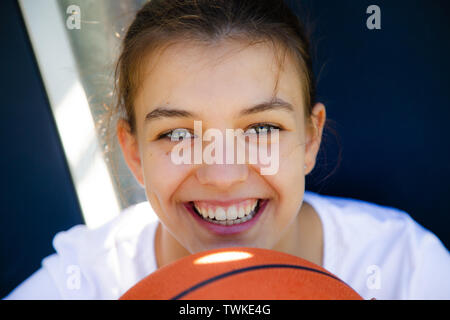 Portrait of a beautiful and young female basketball player smiling - Stock Image
